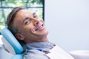 Smiling man shaking hands with dentist