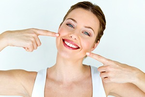 Woman pointing to smile with porcelain veneers