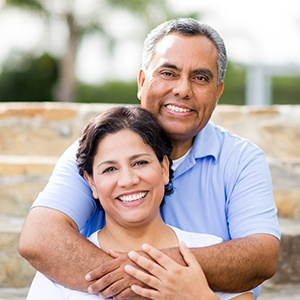 Man and woman smiling after dental crown and fixed bridge restorations