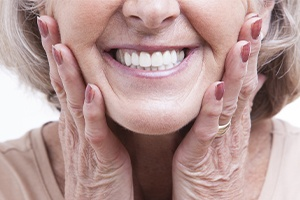 Woman showing off smile after dental bridge placement
