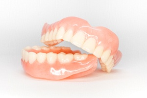Top and bottom full dentures against neutral background