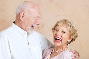 Older man and woman laughing together after dental implant supported tooth replacement