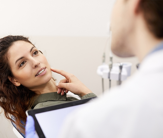 Woman talking to dentist pointing to cheek