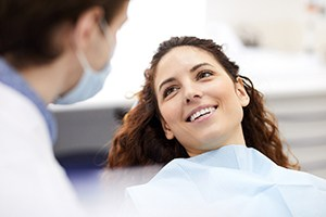 Relaxed female patient smiling during metal-free restoration appointment