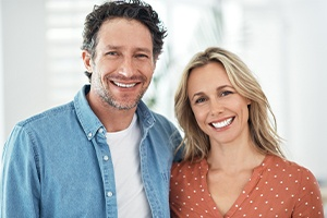 Man and woman smiling after one visit dental restoration