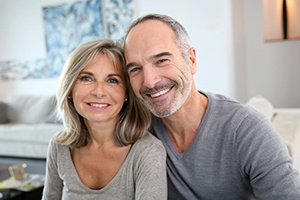 Man and woman sharing smiles after full mouth reconstructions