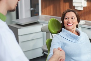 Woman shaking dentist's hand after root canal therapy