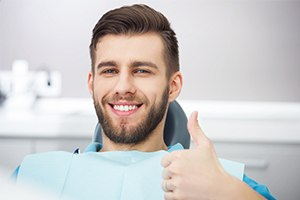 Smiling young man giving thumbs up after wisdom tooth extraction